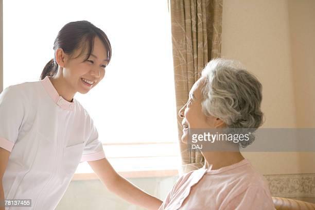 Female nurse talking to senior woman on bed, smiling