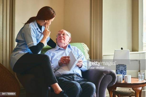 Female nurse talking with senior man at care home