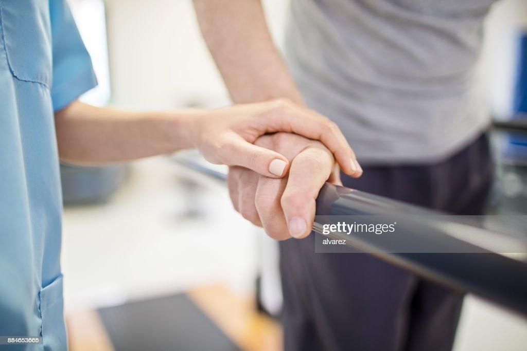 Female nurse touching senior man's hand on railing : Stock Photo