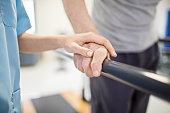 Female nurse touching senior man's hand on railing