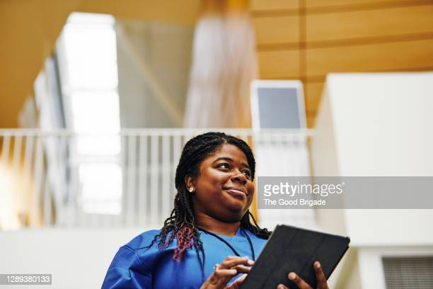 female nurse using digital tablet in hospital corridor - hospital stock pictures, royalty-free photos & images