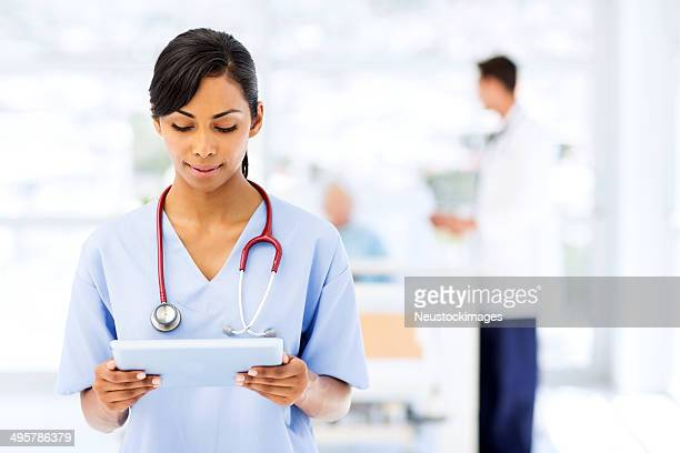 Female Nurse Using Digital Tablet In Hospital