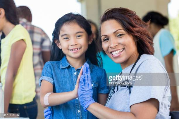 female nurse volunteering at health fair - community volunteer stock pictures, royalty-free photos & images