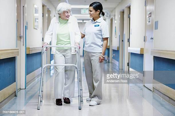 Female nurse walking beside senior woman using orthopedic walker