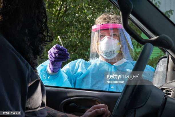 a female nurse wearing a gown, a surgical face mask, gloves, and a face shield swabs the nose of male person of color sitting in his car with a cotton swab in a drive-up (drive through) covid-19 (coronavirus) testing line outside a medical clinic/hospital - drive through stock pictures, royalty-free photos & images