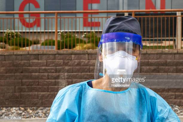 a female nurse wearing a gown, surgical face mask, gloves, and a face shield hands a testing swab to a masked man in his seventies in a drive-up covid-19 testing line outside a medical clinic/hospital outdoors - n95 face mask stock pictures, royalty-free photos & images