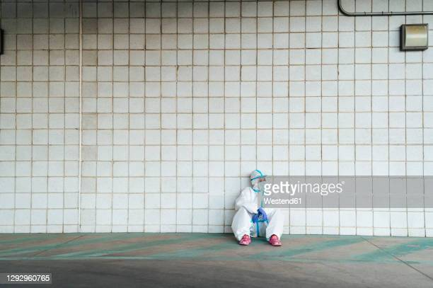 female nurse wearing protective suit with sitting against tiled wall - critical care stock pictures, royalty-free photos & images