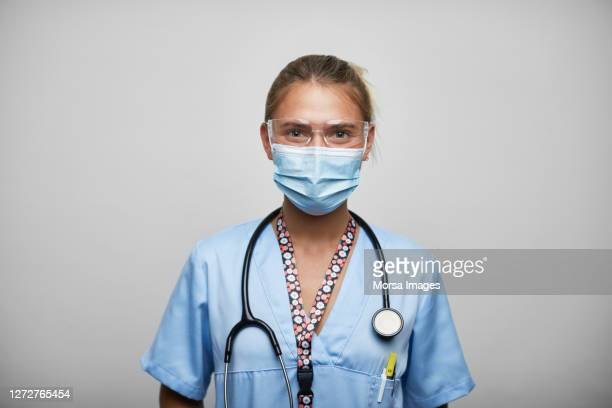 female nurse with face mask on white background - emergencies and disasters stock pictures, royalty-free photos & images