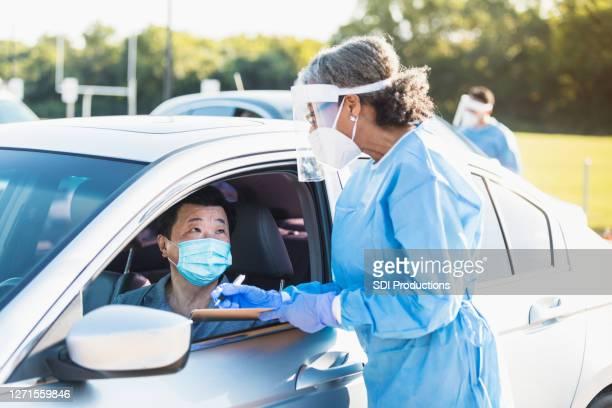 女性看護師は、covid-19試験場で男性に関する情報を書きます - ドライブスルー検査 ストックフォトと画像