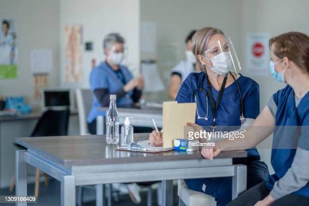 female nurse writing medical notes before administering the covid-19 medical injection - vaccination center stock pictures, royalty-free photos & images