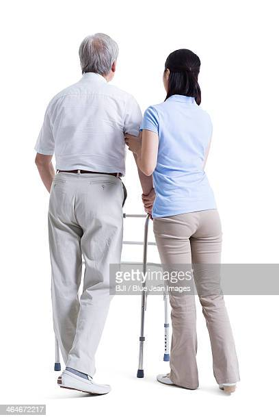 Female nursing assistant helping senior man with walking frame
