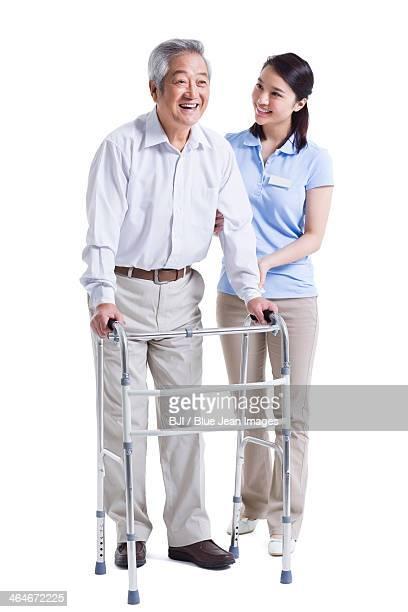 Female nursing assistant helping senior man with walking frame