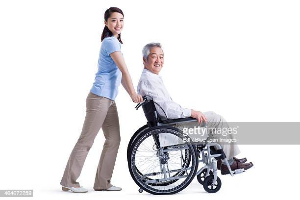 female nursing assistant taking care of senior in wheelchair - nurse and portrait and white background and smiling and female and looking at camera stock pictures, royalty-free photos & images