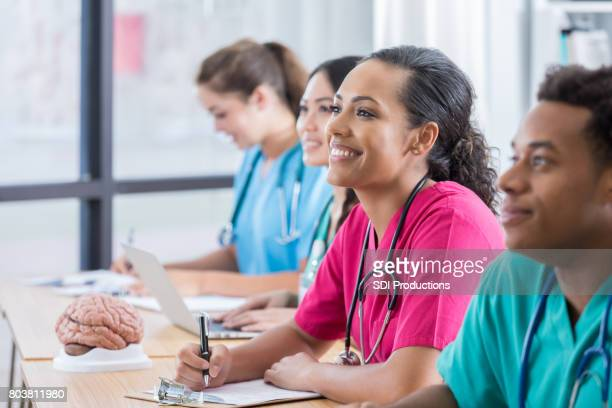 Female nursing student smiles with classmates as they listen to professor