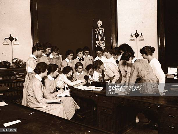 female nursing students watching blood pressure demonstration (b&w) - 20th century stock pictures, royalty-free photos & images