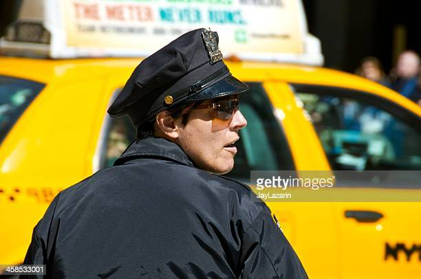 female nypd officer watches over intersection in midtown manhattan, nyc - uniform cap stock photos and pictures