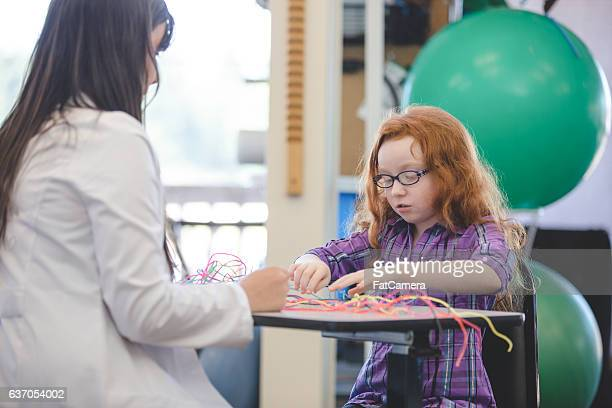 Female occupational therapist helping a child patient inside of a clinic