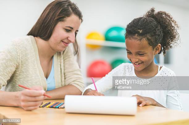 A female occupational therapist is doing rehabilitation with a child patient