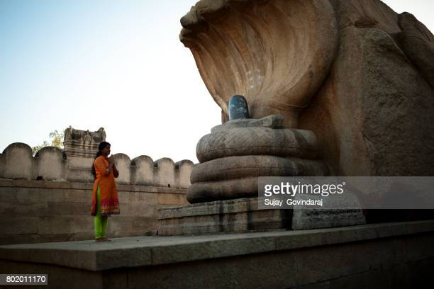 female offering salutation to the hindu serpent god - shiva stock photos and pictures