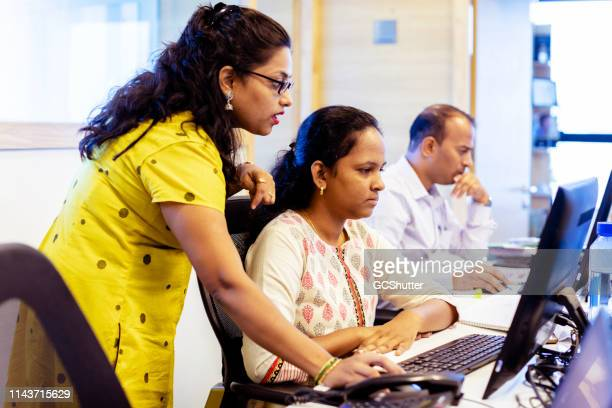 female office manager training new staff about their crm system - indian culture stock pictures, royalty-free photos & images