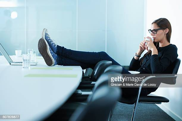 Female office worker drinking coffee with feet up on conference table