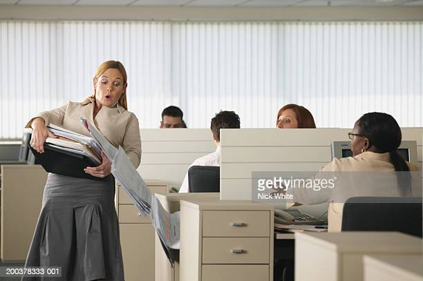 female office worker dropping pile of documents in office - down blouse stockfoto's en -beelden
