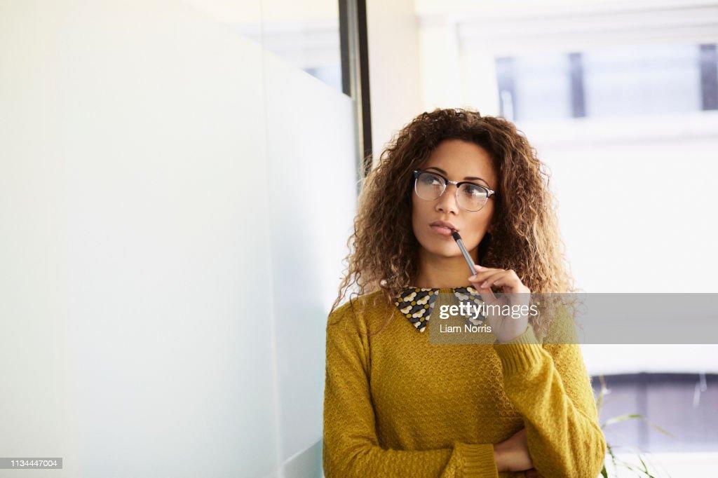Female office worker holding pen : Stock Photo