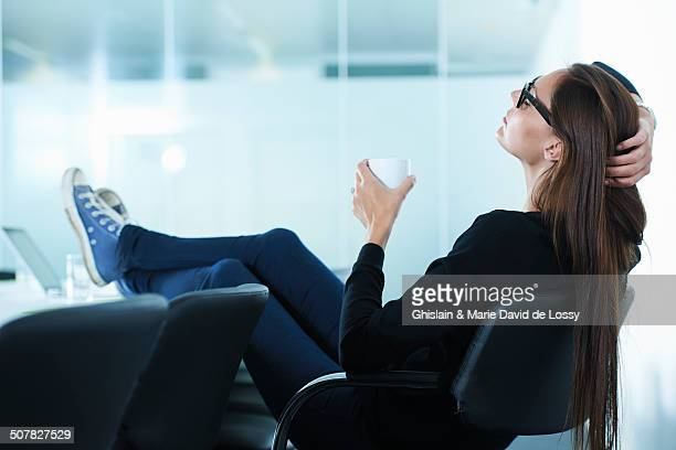 Female office worker leaning back with feet up on conference table
