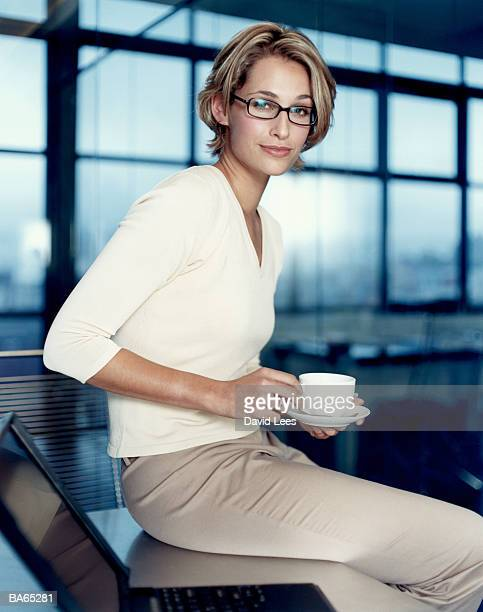 Female office worker on desk with laptop, holding tea cup, portrait
