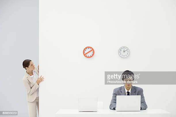 Female office worker peeking around corner at clocks on wall, colleague looking down at laptop