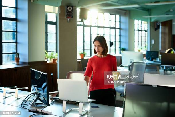 female office worker switching on computer to start her working day - beginnings stock pictures, royalty-free photos & images