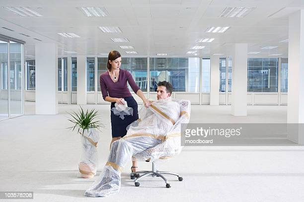 Female office worker unwrapping office worker in empty office space