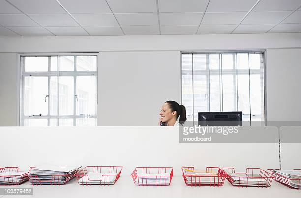 female office worker using telephone, smiling, in office cubicle behind trays with documents - inbox filing tray stock pictures, royalty-free photos & images