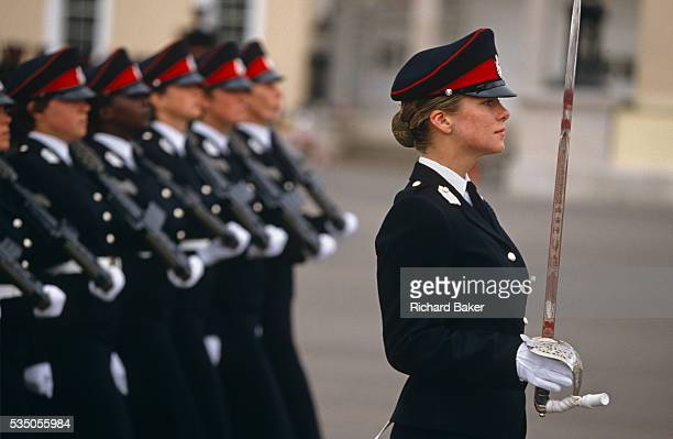 Female officer cadets march in line with their weapons on shoulders past guests and VIPs at their passing out parade in the Royal Military Academy...