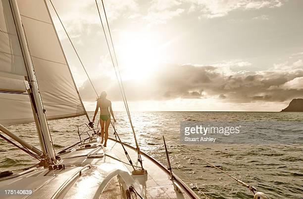 Female on bow of sailing yacht, Whitsundays sunris