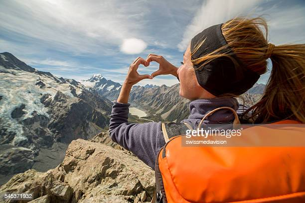 Female on mountain top makes heart frame towards Mount Cook
