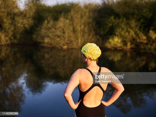 female open water swimmer by a lake - swimming stock pictures, royalty-free photos & images