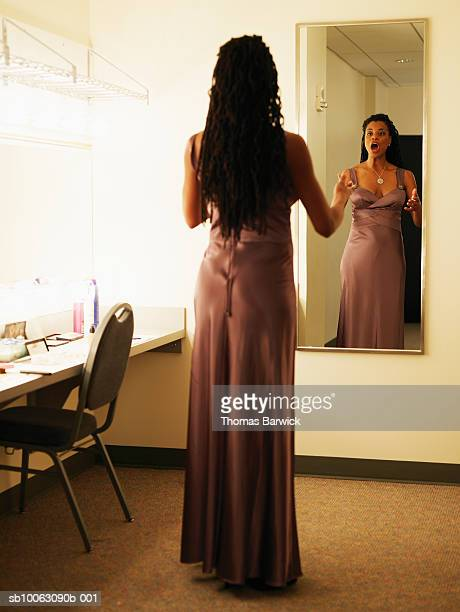 Female opera singer warming up in dressing room mirror