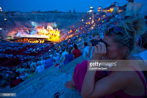 Female operagoer are looks around with binoculars while sitting on the stone steps in the Arena of Verona on July 14 2010 in Verona Italy The famous...