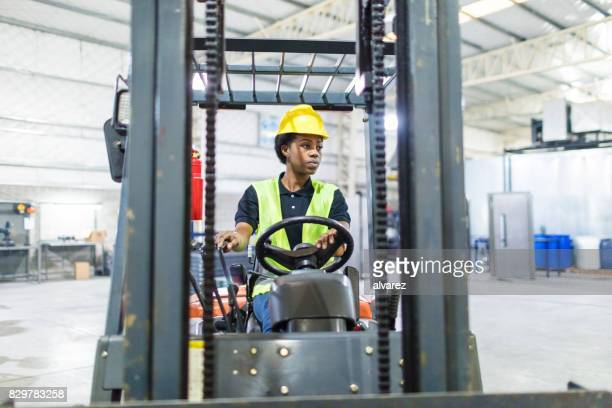 Female operator driving forklift in factory