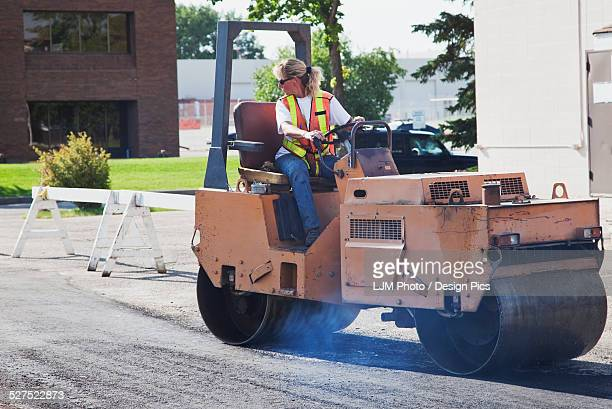 Female operator driving steam roller repairing pot holes in a parking lot