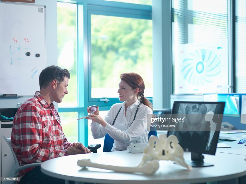 Female orthopaedic consultant with patient in consulting room : Stock Photo