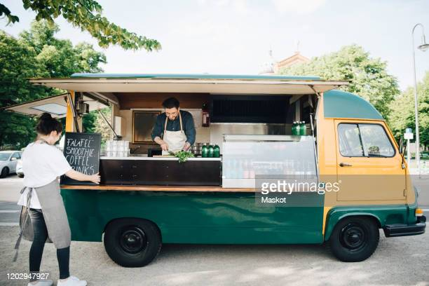 female owner adjusting board on concession stand while partner working in food truck - food truck stock pictures, royalty-free photos & images