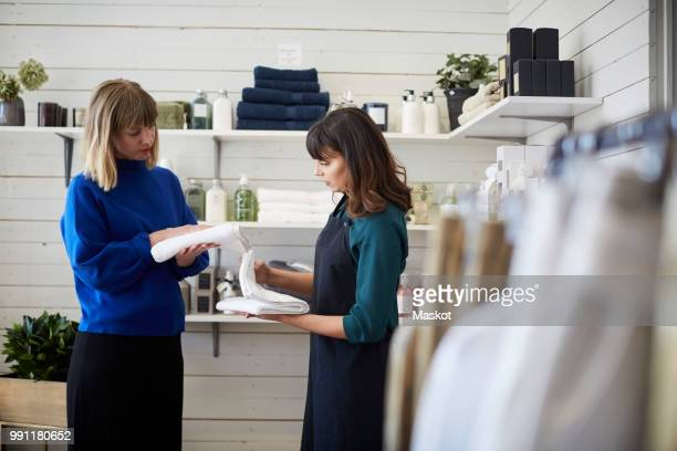 female owner assisting customer in choosing textile at store - household equipment stock pictures, royalty-free photos & images