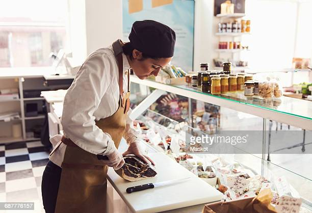 female owner cutting meat at counter in grocery store - delicatessen stock pictures, royalty-free photos & images