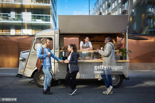 female owner in concession stand while customers having food and drink on street in city - food truck fotografías e imágenes de stock