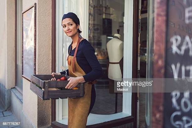 Female owner looking away while carrying vegetable crate at entrance of grocery store