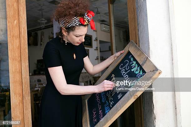 Female owner of oil bar writing menu on blackboard