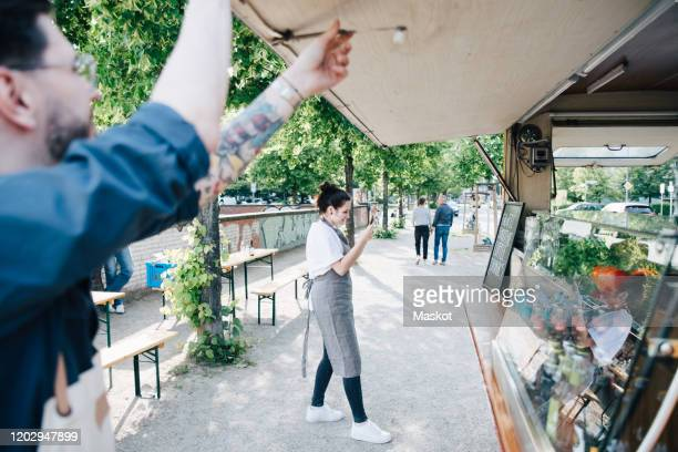 female owner photographing board through smart phone while male coworker opening shade of food truck - apron stock pictures, royalty-free photos & images