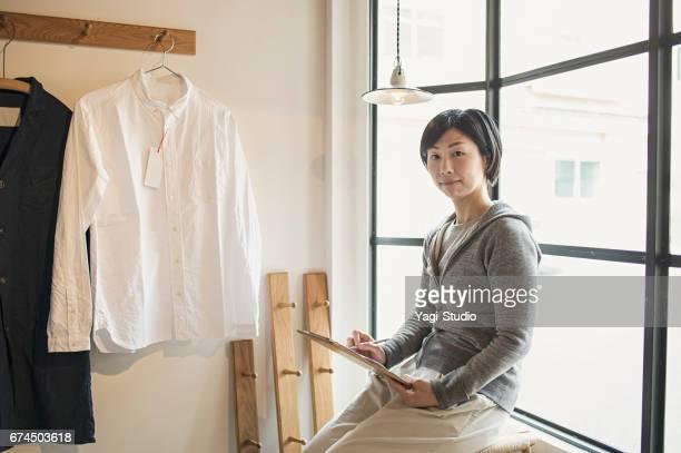 女性経営者は、一般のお店で店をオープンする準備をしてします。
